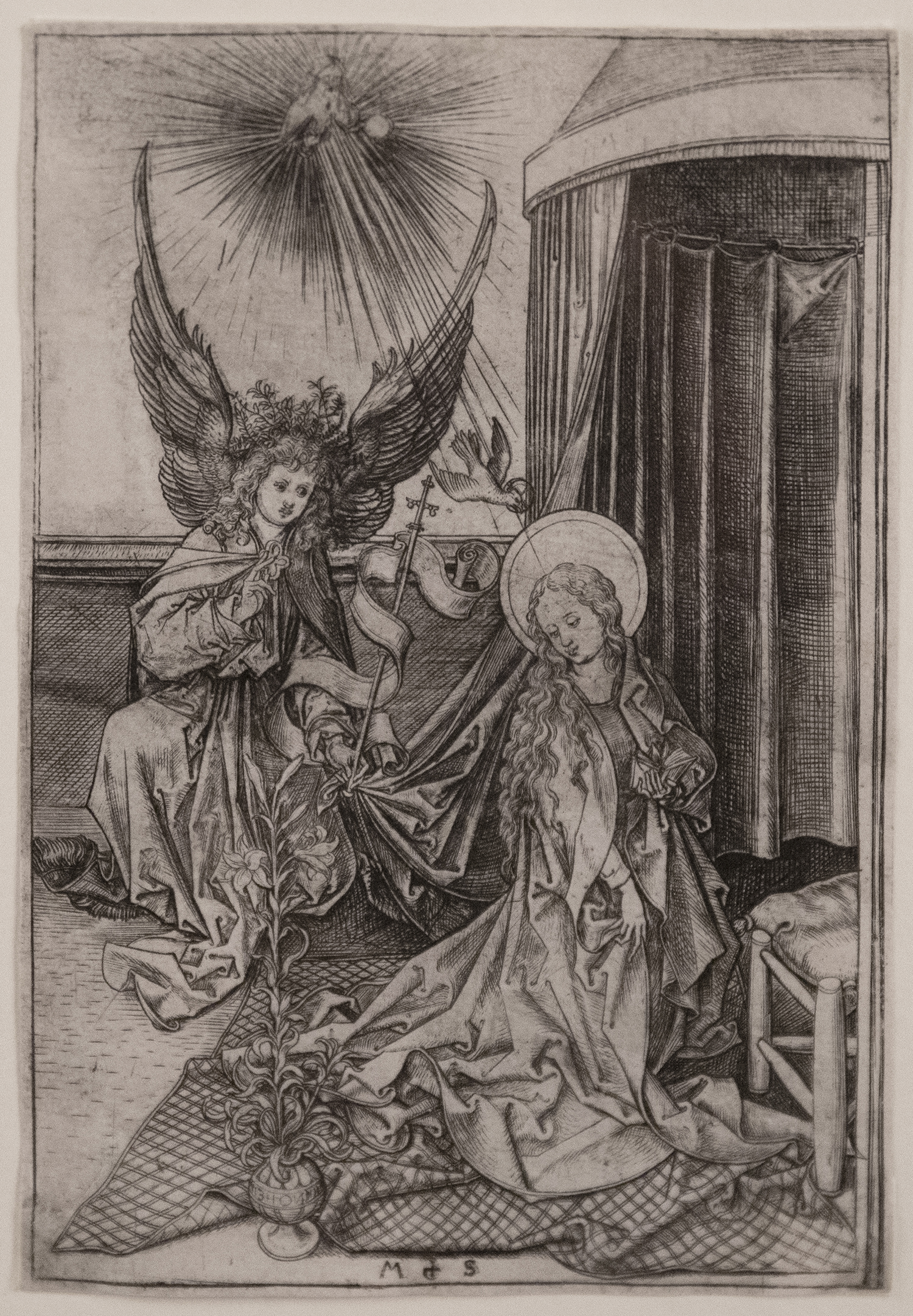 A winged angel standing and speaking to a woman sitting next to a tent.