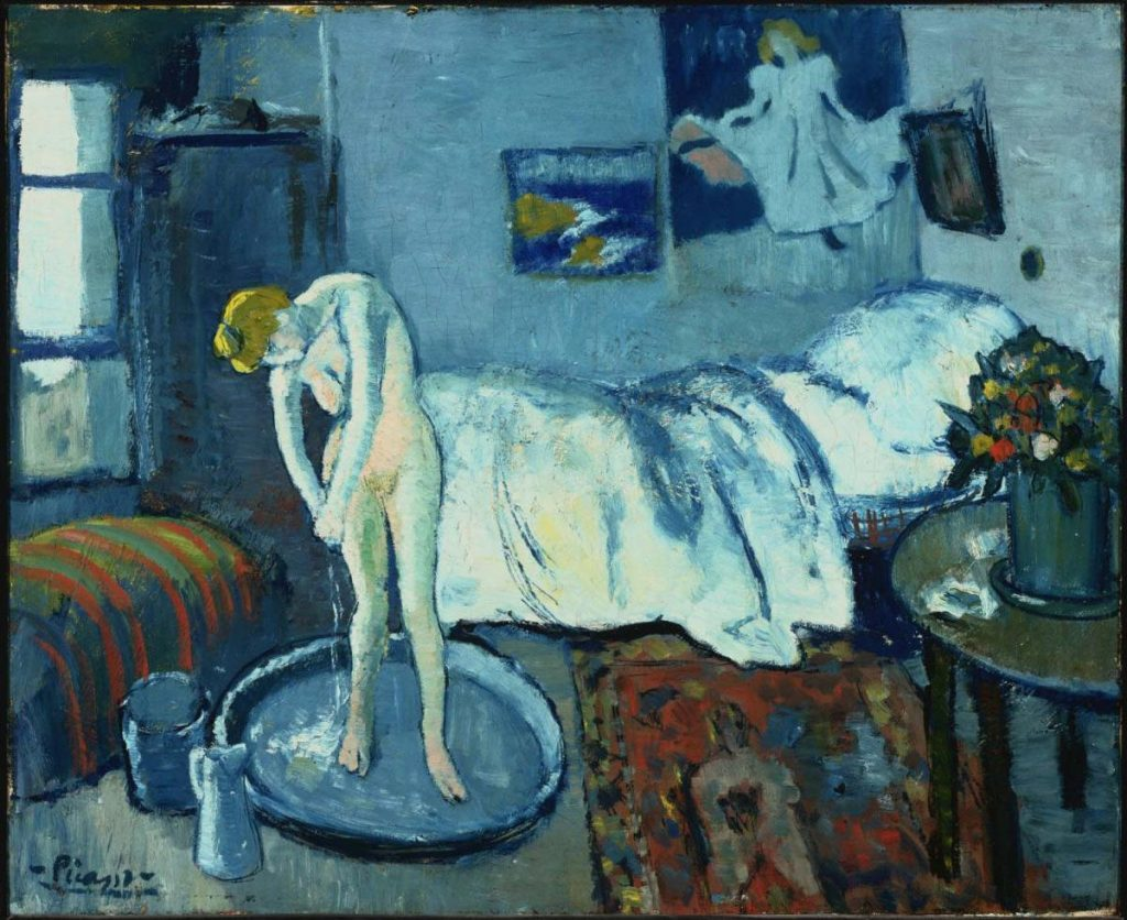 A nude woman bathes in a washtub in a bedroom. Posters hang on the wall behind her. The room is washed in various shades of blue.