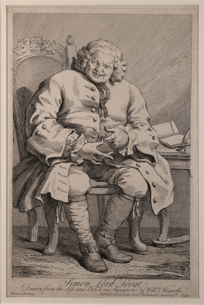 An older man wearing a fancy overcoat, sitting in a chair, looking at the viewer; a book and quill sit on the desk to the right.