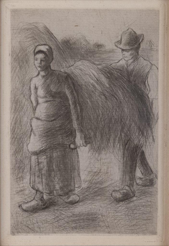 A man and woman in peasant dress carry a bale of hay between them.