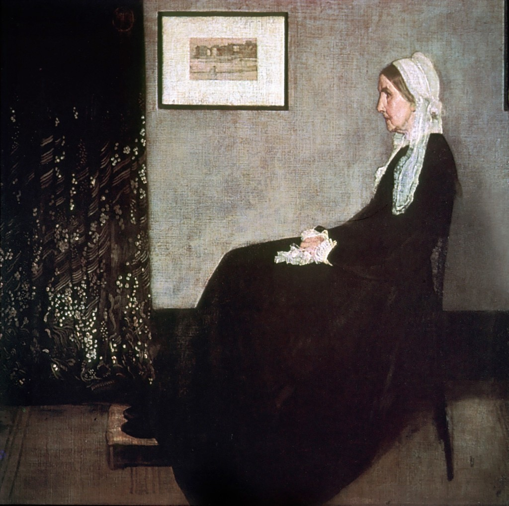 A seated woman is shown in side profile. She is dressed in black and wears a white veil. A framed image is hung on the gray wall behind her.