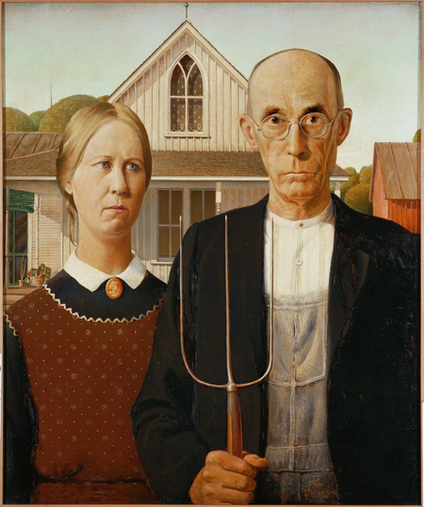 A man and woman stand in front of  a farm house. Their expressions are solemn and the man holds a pitchfork.