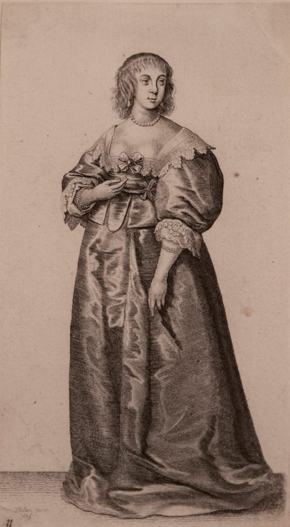 Young English noblewoman wearing large, ornate dress and pearl necklace.
